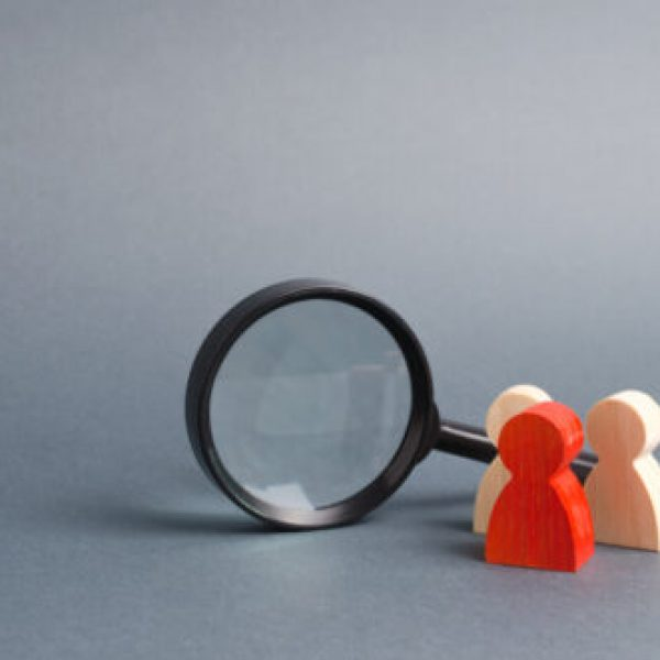 Three,Wooden,Human,Figure,Stands,Near,A,Magnifying,Glass,On
